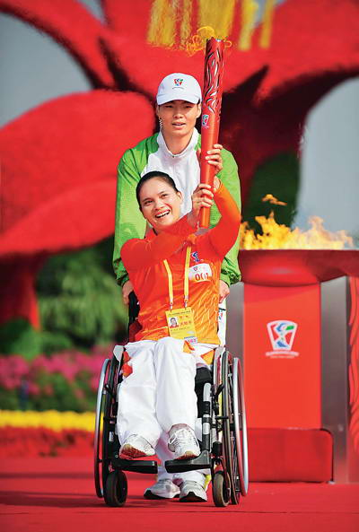 第一棒火炬手、2008年北京残奥会反曲弓公开级金牌获得者符洪芝高举火炬从花城广场出发。新华社记者 梁旭摄