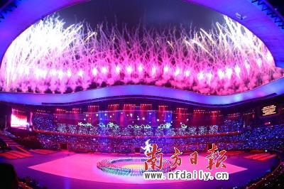"""昨晚,广州亚残运会会徽造型的""""巨人""""在开幕式前的倒计时表演中从天而降,绚丽烟花瞬间绽放。南方日报记者张由琼王辉摄"""