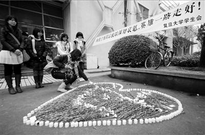 12月14日,复旦大学学生将鲜花和蜡烛摆放成心形,悼念遇难民警张宁海。新华社发