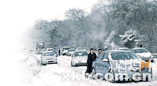 ■英国南部,主干道上汽车大排长龙,道路结冰,不少人下来推车。