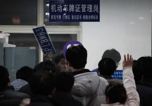 12月22日,北京崔各庄附近检测场办公大厅内,工作人员正在发放车牌。由于日前有传闻称,北京出台的治堵新政会对市民买车不利,准备领牌照的人突然增多,更有车主凌晨三四点就开始排队。CFP 图