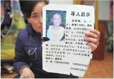 11月29日,唐娟拿着当年寻找女儿的寻人启事,不禁潸然泪下。 记者 伍霞 摄