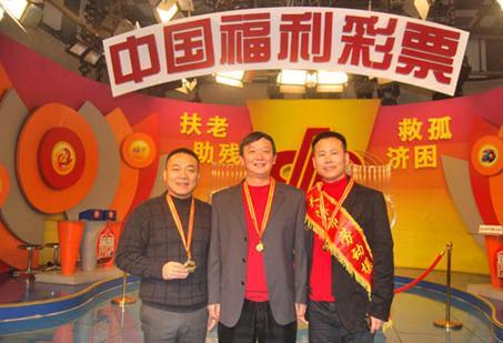 天津福彩中心主任柳建军与奥运会冠军楼云、残奥会冠军孙长亭在双色球现场合影