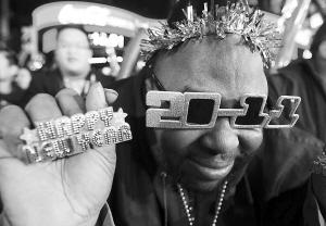 """2010年12月31日,在美国纽约时报广场,一名男子头戴2011年字样墨镜,手持""""新年快乐""""的字样,参加迎接新年的庆祝仪式 新华社 发"""