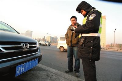 一辆天津牌照的车辆违反限行规定在四方桥被拦下接受处罚