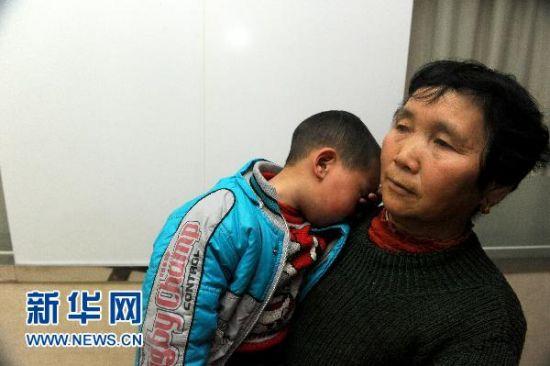1月5日,在安徽省立儿童医院,安徽省安庆市怀宁县高河镇一名家长抱着孩子。新华社记者 郭晨 摄