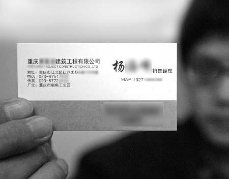 业务员杨先生展示自己的名片,上面的头衔为销售经理。 记者 张永波 摄
