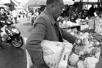一市民夹着刚买来的一袋大米,又在菜摊上挑选蔬菜 晚报记者 任国强 现场图片