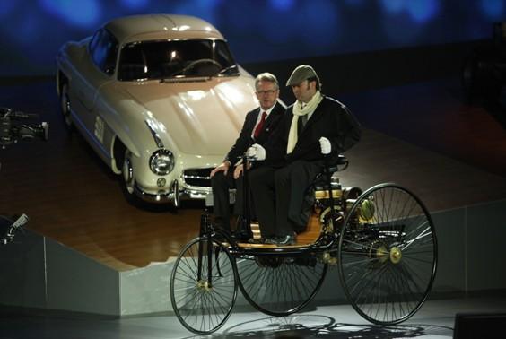 华立新先生驾驶着当年卡尔-奔驰发明的第一辆专利汽车缓缓驶上舞台