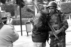 18日,突尼斯,一名男子亲吻街头巡逻的士兵。