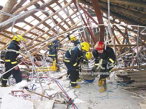 消防人员用手将废墟一点点清理干净,并利用气动液压撑顶器将压住工人图片