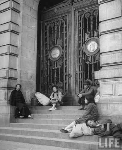 遵义新浦新区最新-一个穷苦的家庭坐在关了门的银行的阶梯上,1945年上海,George