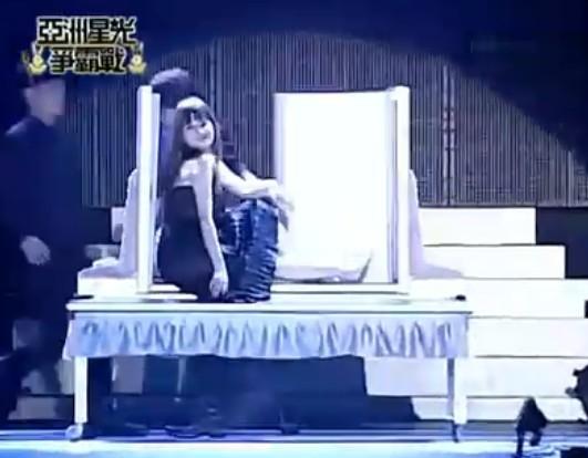 在另一段魔术中,一位美女坐在两块木板之间。