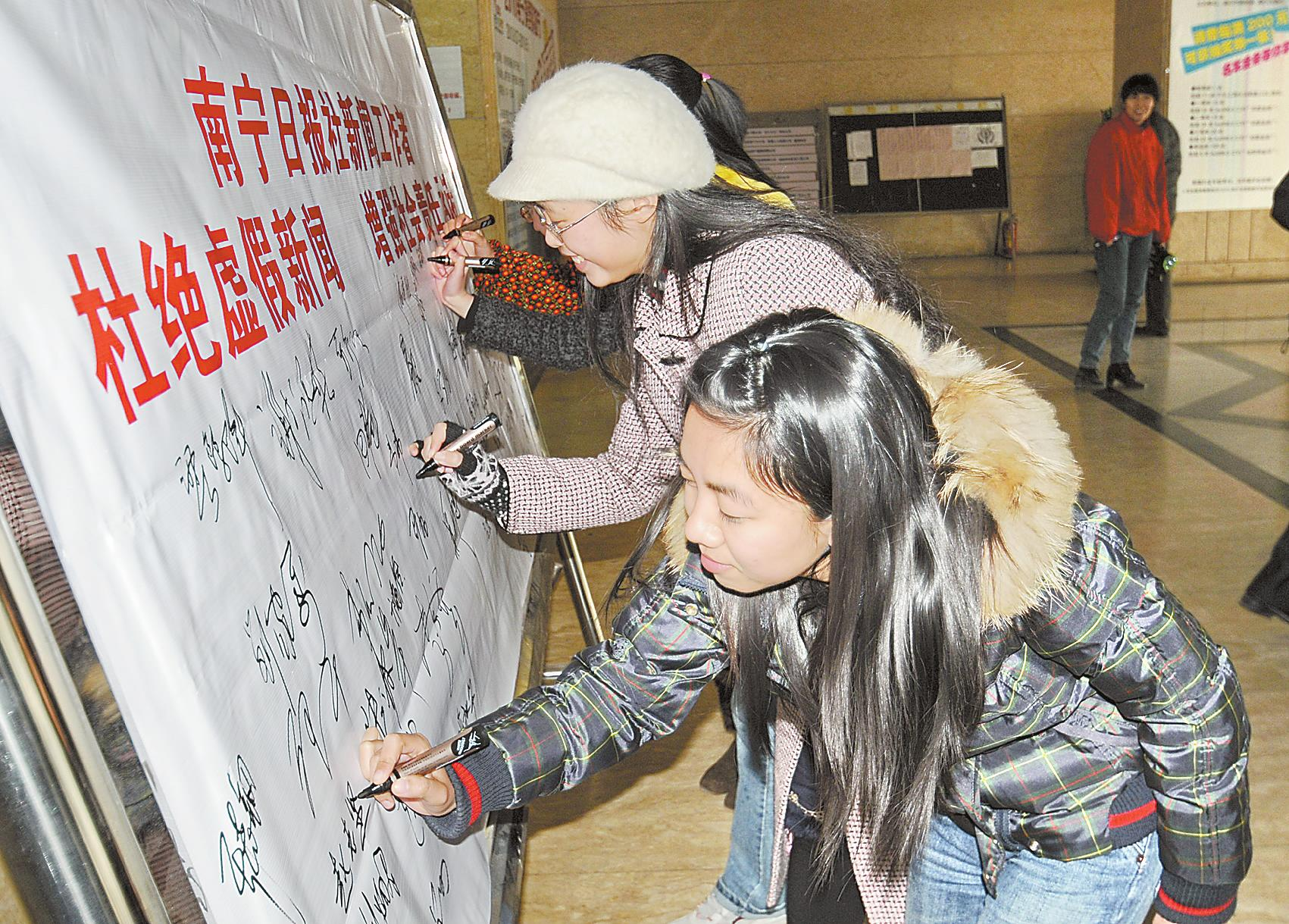 报社新闻采编人员在展板上签名承诺杜绝虚假报道,增强社会责任.