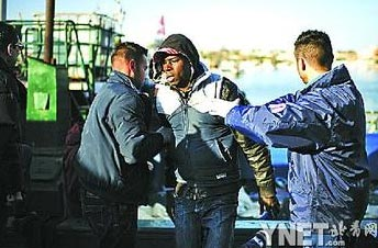 13日,意大利西西里地区兰佩杜萨岛,一名突尼斯非法入境移民下船登岸 ■新华/法新
