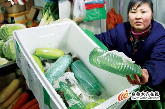 2月13日,在青年路农贸市场,卖菜人梁秀英展示蔬菜包装箱内装的水瓶。(记者 丁瑜 摄)