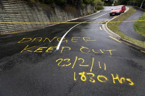 地震后地面上喷涂的警示-新西兰克莱斯特彻奇震后景象 巨石砸毁路牌