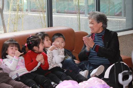 (图一)在报到现场,一位陪同参赛的老奶奶组织4名小选手在沙发上唱起了儿歌