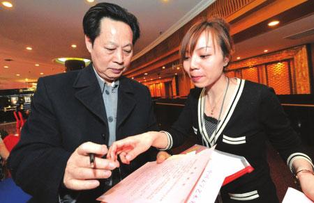 一名北京国际饭店委员驻点的医疗组工作人员(右)向全国政协委员汪国新发放健康提示卡新华社发