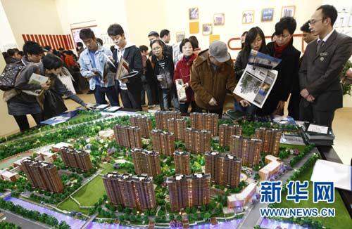 """市民正在上海之春房展会上参观楼盘模型(2010年3月18日摄)。1月27日,备受关注的上海房产税试点细则""""浮出水面""""。上海市人民政府当日印发《上海市开展对部分个人住房征收房产税试点的暂行办法》,于28日起对上海居民家庭新购第二套及以上住房和非上海居民家庭的新购住房征收房产税,税率因房价高低分别暂定为0.6%和0.4%。新华社记者 裴鑫 摄"""