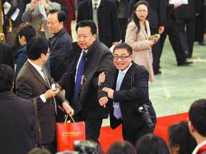 拽紧了  一名记者在人群中认出了中国银监会主席助理阎庆民,挽着胳膊,把他拉到采访区。