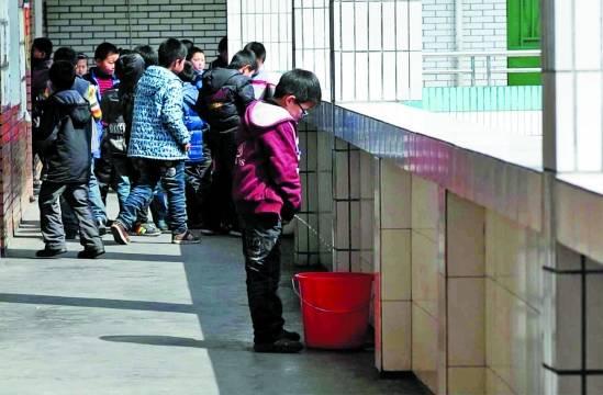 东阳一小学走廊上放着许多用来接童子尿的水桶,男孩们对此早有默契。
