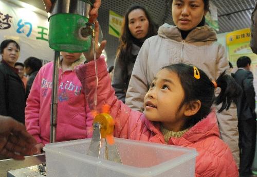 在广西科技馆举行的广西青少年科技创新大赛作品展厅,一名小学生观看图片