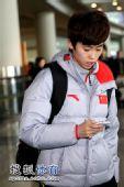 图文:短道速滑队载誉抵京 范可新看手机