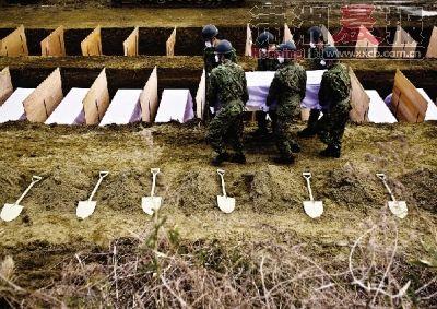 23日,日本宫城县东松岛市,日本自卫队队员将海啸遇难者集体安葬。图/CFP