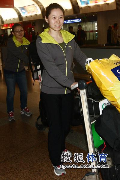 图文:中国冰壶女队载誉归国 于鑫娜推着行李