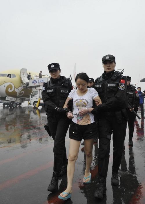4月1日,罪嫌疑人王婉宁被特警押解下飞机.新华社发