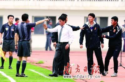 因对裁判的判罚不满,李章洙(中)的教练组与裁判发生争执。  朱小龙 摄