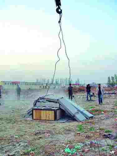 在郑州东郊一个厂区,吊车依次吊起16块预制板砸向空地上的床。