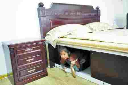 """任先生的女儿曼曼向大家演示这张床如何把人""""保护""""进床箱里"""