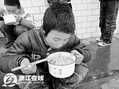 孩子们在屋外冒雪吃饭。