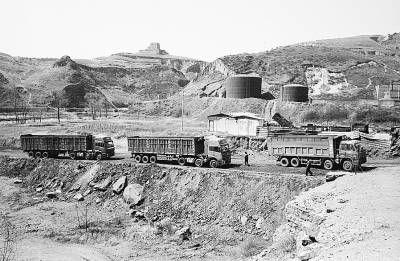 2011年4月17日,陕西省府谷县县级文物保护单位新民龙王庙墩台下,运煤车来来往往。