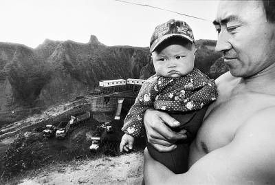 山坡上,来自延安的矿工小刘抱着6个月的女儿忧心忡忡。头一天,煤矿雇用20多人毒打龙王庙村上访的村民,多人被送到医院。