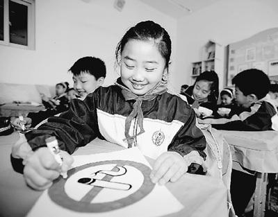 """日前,辽宁省沈阳市振兴街第二小学举行""""校园远离香烟""""主题活动。当天,千余师生亲手制作并悬挂禁烟标志,杜绝香烟进入校园。沈乐洵摄(人民图片)"""