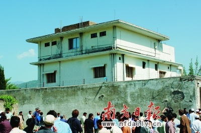 """5月3日,在巴基斯坦阿伯塔巴德,人们聚集在""""基地""""组织领导人本·拉丹遭袭地点。 新华社发"""
