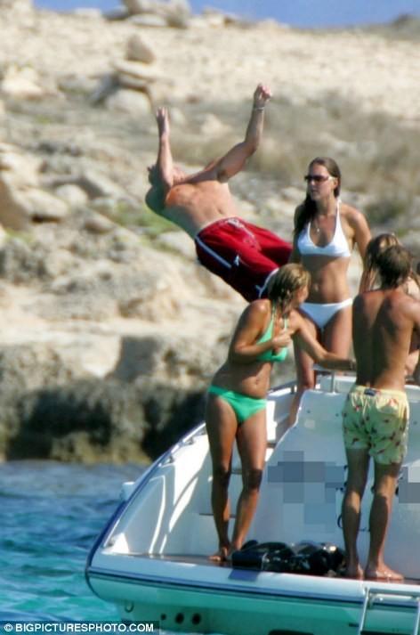 身穿红色泳裤的威廉准备以后空翻的姿势入水