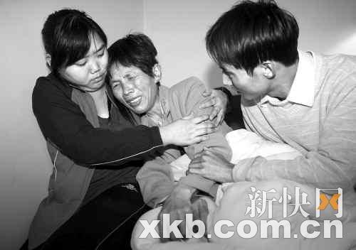 失事工人徐瑞祥的老婆(中)坐在床上痛哭,家人在一旁安慰。