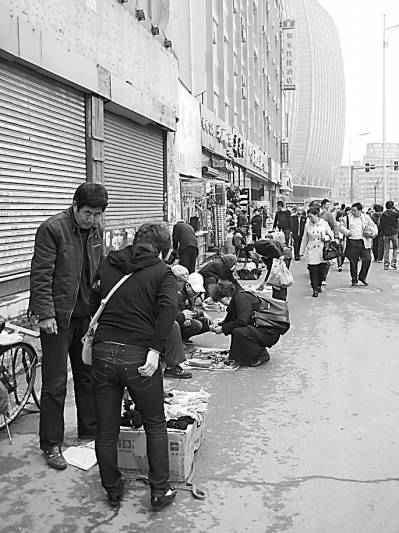 在夏俊峰摆摊出事的地点,风雨坛街两侧三三两两的摆摊者依然聚集着,往来询问购买者也络绎不绝。