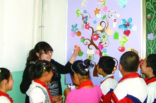 巴彦淖尔路小学四年级(2)班的同学们在课间将自己的心愿贴到心愿墙上.图片