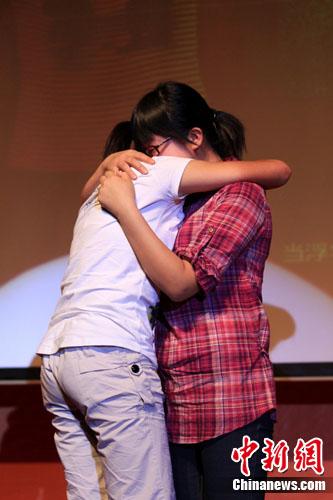 """妹妹何容(左)给姐姐何玲(右)颁奖时,紧紧抱住姐姐,泣不成声。何容说,姐姐在她心中,更像是一位""""母亲""""。刘函冉 摄"""