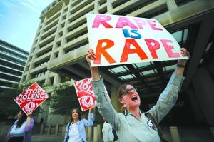 5月18日,美国华盛顿的市民聚集在国际货币基金组织大楼前举牌声讨涉嫌性侵犯的卡恩。