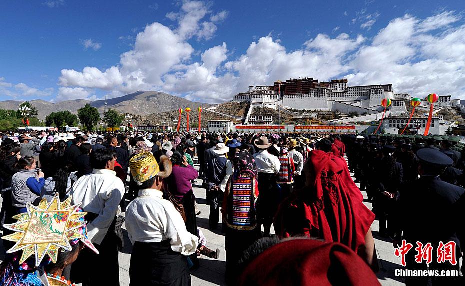"""5月23日,西藏和平解放60周年""""升国旗、唱国歌""""仪式在拉萨布达拉宫广场举行,5000多名各族各界群众参加活动。 图为布达拉宫广场上国旗徐徐升起。李林 摄"""
