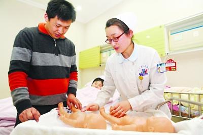 产科护理人员用模型教新爸爸做婴儿抚触操。
