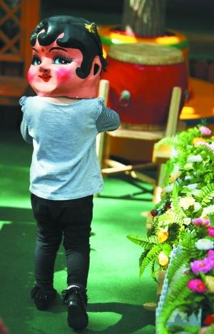 场景:小女孩戴着大头娃娃的头套玩