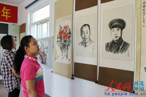 图为正在参观抗大学员书画展览的群众.朱娜摄图片