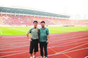姜峰(左)与记者在天河体育场合影。